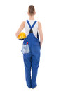 Rear view of young attractive woman builder in blue workwear is isolated on white background Royalty Free Stock Photo