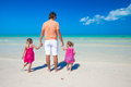 Rear view of young father and his two adorable daughters on an exotic vacation Stock Photo