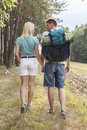 Rear view of young hiking couple holding hands while walking in countryside Royalty Free Stock Photography