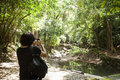 Rear view of young male hiker photographing in forest koh pha ngan thailand Royalty Free Stock Image