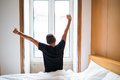 Rear view of a young man waking up in bed and stretching his arms in the morning Royalty Free Stock Photo