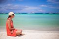Rear view of young sexy woman in hat sitting on white sand beach this image has attached release Stock Image