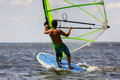 Rear view of young windsurfer man windsurfing in splashes water Royalty Free Stock Photos