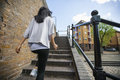 Rear view of young woman walking up stairs Royalty Free Stock Photo