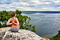 Rear view of young woman in yoga pose sitting on the rock above river. Royalty Free Stock Photo