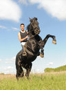 Rearing horse young man and her beautiful black stallion up Stock Photo