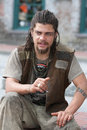 Rebel with dreadlocks and tattoos sitting outside Royalty Free Stock Images