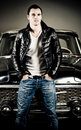 Rebel type guy with leather jacket posing in front of an oldtimer Stock Images