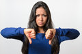 Rebellious negative woman giving a thumbs down gesture with frown to show her displeasure and register no vote Royalty Free Stock Photos