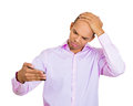 Receding hairline closeup portrait shocked man feeling head surprised he is losing hair or seeing bad news on cellphone isolated Royalty Free Stock Images