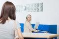 Recepcionista looks at woman en la oficina del dentista Imágenes de archivo libres de regalías