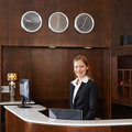 Receptionist behind counter at hotel happy female Stock Image