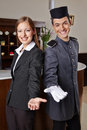 Receptionist and bellboy in hotel offering welcome smiling happy a Stock Photo