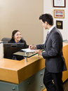 Receptionist greeting man at front desk Stock Photos