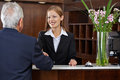 Receptionist greeting senior guest with handshake smiling female a Stock Photos