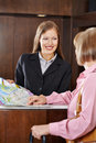 Receptionist in hotel offering city map happy female to senior guest Stock Image