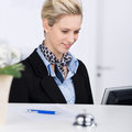 Receptionist using computer at desk portrait of confident smiling while Royalty Free Stock Image