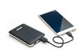 Recharging smart phone tablet from power bank isolate Royalty Free Stock Photo