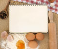 Recipe book with flour eggs and rolling pin on a wooden table Royalty Free Stock Photos