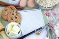 Recipe book and ingredients for baking fresh oatmeal cookies with fresh cookies spices pen paper room text Stock Image