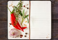 Recipe book open with chili and spices on a wooden background Royalty Free Stock Photos