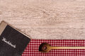 Recipe book and wooden spoon on a checkered table cloth Stock Image