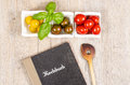 Recipe book and wooden spoon with tomatoes basil as ingredients Royalty Free Stock Images