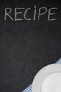 Recipe title is written in chalk on a blackboard and plate on na napkin the bottom corner vertical Royalty Free Stock Photo
