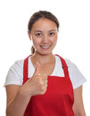 Recommending chinese waitress smiling in a red apron showing her thumb Stock Photo