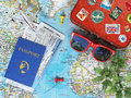 Recreation and travel concept old suitcase for plane sunglasses passport with air tickets palms on the world map Stock Images