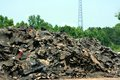 Recycle a pile of roofing material to be recycled with a communications tower in the background Stock Photos
