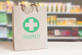 Recycled paper bag with a green Pharmacy logo in a drugstore. Empty copy space Royalty Free Stock Photo