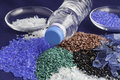 Recycled plastic polymers out of pet water bottle bottles in red blue green and black colours Stock Photo