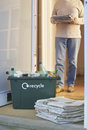Recycling container and pile of waste papers closeup on floor with person in background Stock Photos
