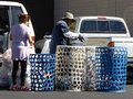 Recycling at a local center in chatsworth california woman with several large bags of plastic bottles is assisted by employee Royalty Free Stock Image