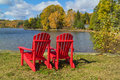 Red Adirondack Chairs on a Lake Shore Stock Image