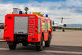 Red airport fire truck driving on the tarmac in front of the incoming airplane Royalty Free Stock Photos