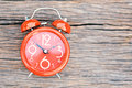 Red alarm clock on old wood background