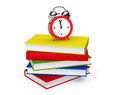Red alarm clock standing on stack of books a white background Stock Image