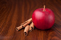 Red apple on dark wooden table with sticks of cinnamon Royalty Free Stock Photography