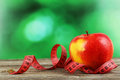 Red apple with measuring tape on grey wooden background.
