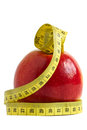 Red apple with measuring tape over white background the concept of diet and fitness Stock Photography