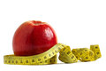 Red apple and measuring tape over white background the concept of diet fitness Royalty Free Stock Image