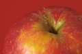 Red apple one juicy hot over a colored background Royalty Free Stock Image