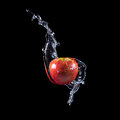 Red apple splashing into water on dark background Royalty Free Stock Images