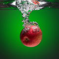 Red apple splashing into water on the green background Stock Photography