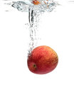 Red apple splashing into water on the white background Royalty Free Stock Photo