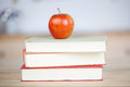 Red apple on stacked books on table closeup of Royalty Free Stock Image