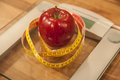 Red apple and tape measure on weight scale. Royalty Free Stock Photo