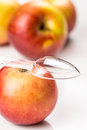 Red apple and translucent medicine spoon on the table symbolising that drinking eating of products prevents diseases Royalty Free Stock Photo